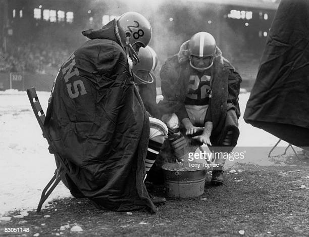Cleveland Browns end Dick Deschaine and halfback Ken Konz warm themselves over a Coca Cola bucket filled with charcoal on a cold day in Clevelend in...