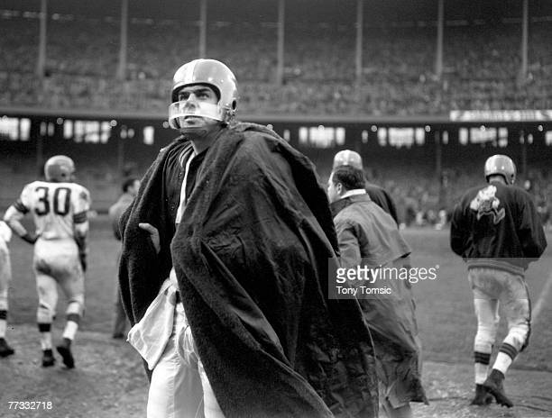 Cleveland Browns Hall of Fame quarterback Otto Graham tries to stay warm and dry on a cold, muddy day during a 24-14 victory over the New York Giants...
