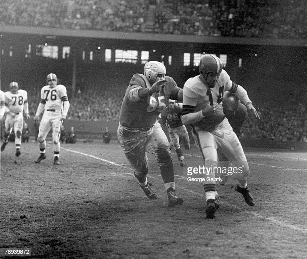 Cleveland Browns Hall of Fame quarterback Otto Graham trying to avoid being tackled in a 177 loss to the Detroit Lions in a League Championship game...