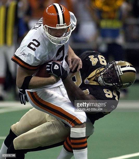 Cleveland Browns' quarterback Tim Couch is stopped on a third down attempt by New Orleans Saints' Charles Grant in the first quarter 24 November 2002...