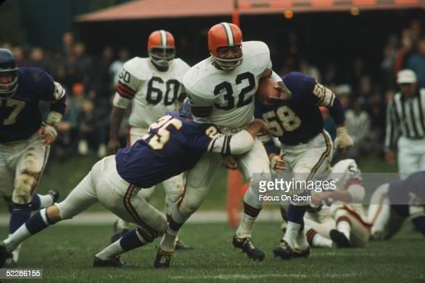 Cleveland Browns' running back Jim Brown runs through a tackle