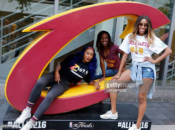 Cleveland Cavaliers fans pose with a Cavs logo outside Quicken Loans Arena before the start of Game 6 of the NBA Finals between the Golden State...