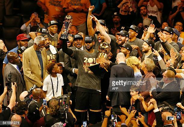 TOPSHOT Cleveland Cavaliers forward LeBron James hoists the Larry O'Brien and the Finals MVP trophies after defeating the Golden State Warriors to...