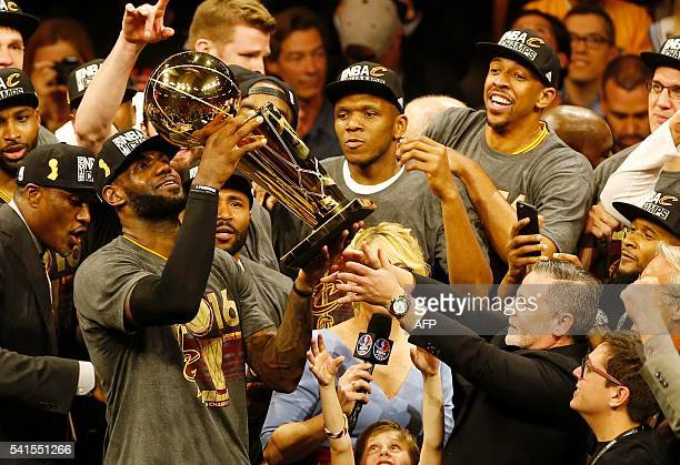 TOPSHOT Cleveland Cavaliers forward LeBron James hoists the Larry O'Brien trophy after defeating the Golden State Warriors to win the NBA Finals on...