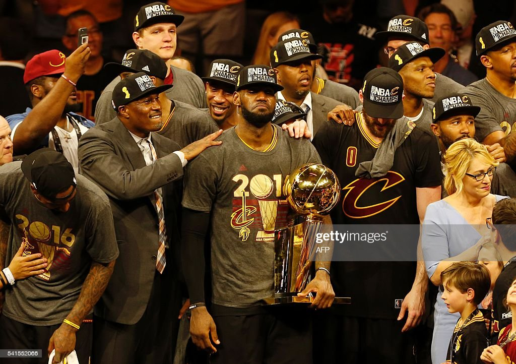 Cleveland Cavaliers forward LeBron James reacts while holding the Larry O'Brien trophy after defeating the Gold State Warriors to win the NBA Finals on June 19, 2016 in Oakland, California. Powered by an amazing effort from LeBron James, the Cleveland Cavaliers completed the greatest comeback in NBA Finals history, dethroning defending champion Golden State 93-89 to capture their first NBA title. The Cavaliers won the best-of-seven series 4-3 to claim the first league crown in their 46-season history and deliver the first major sports champion to Cleveland since the 1964 NFL Browns, ending the longest such title drought for any American city. / AFP / Beck Diefenbach