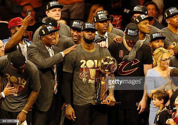Cleveland Cavaliers forward LeBron James reacts while holding the Larry O'Brien trophy after defeating the Gold State Warriors to win the NBA Finals...