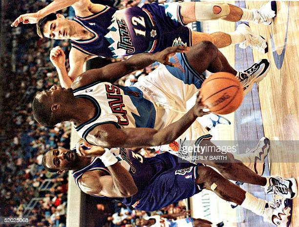 Cleveland Cavaliers forward Shawn Kemp feels the defensive pressure of Karl Malone and John Stockton in the final minutes of game action 21 December...