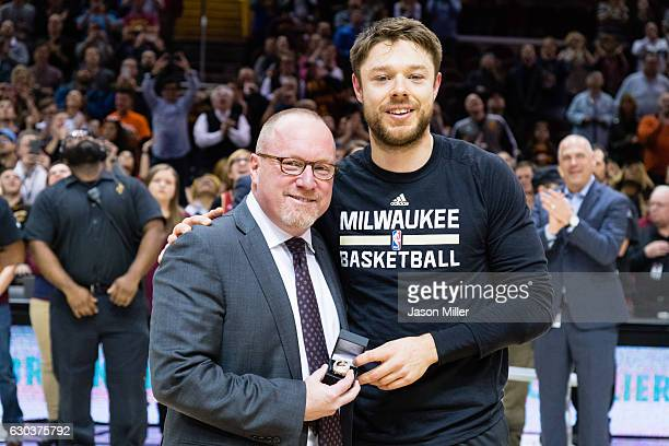 Cleveland Cavaliers general manager David Griffin presents former Cavalier Matthew Dellavedova of the Milwaukee Bucks with his championship ring...