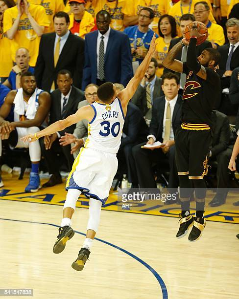 Cleveland Cavaliers guard Kyrie Irving makes a threepoint shot over Golden State Warriors guard Stephen Curry to take the lead in the final moments...
