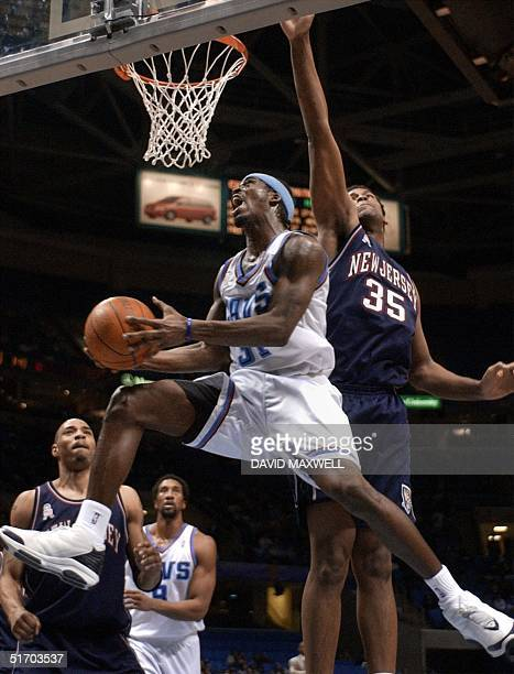 Cleveland Cavaliers' guard Ricky Davis drives to the basket as New Jersey Nets' center Jason Collins defends during the third quarter 19 March 2002...