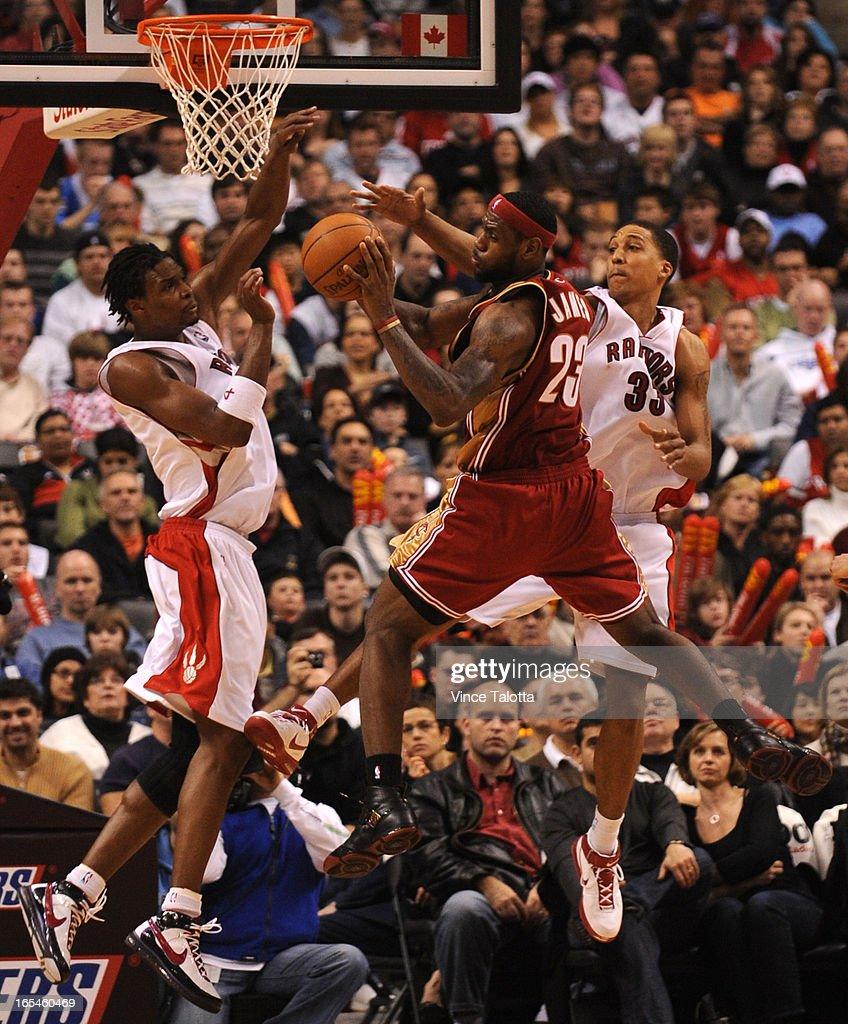 01/06/2008 - Cleveland Cavaliers Lebron goes to the net against Toronto Raptors Chris Bosh and Jamar : News Photo
