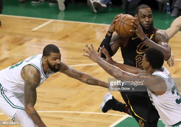 Cleveland Cavaliers LeBron James drives to the basket in between Boston Celtics Marcus Morris and Marcus Smart during fourth quarter action The...