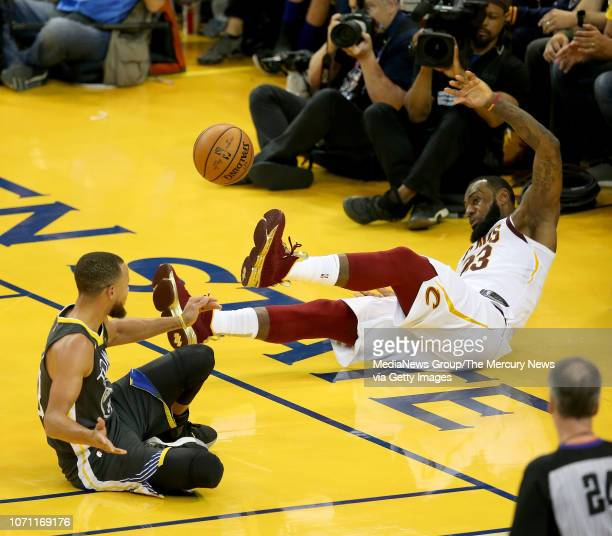 Cleveland Cavaliers' LeBron James falls out of bounds as he's guarded by Golden State Warriors' Stephen Curry and James was called for a technical...