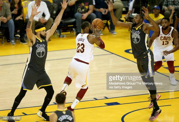Cleveland Cavaliers' LeBron James is double teamed by Golden State Warriors' Kevin Durant and JaVale McGee as he passes to Tristan Thompson during...