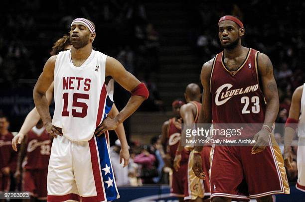 Cleveland Cavaliers' LeBron James walks past as New Jersey Nets' Vince Carter sighs after missing a free throw in the final seconds of the fourth...