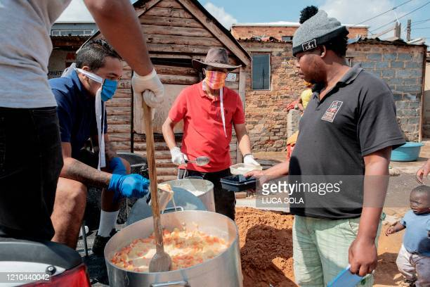 Cleveland Civic Committee volunteers distribute hot meals during the daily food distribution in the Mangolongolo informal settlement, near...