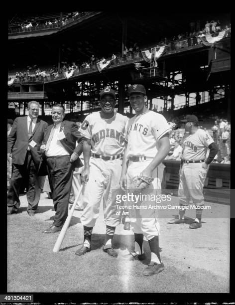 Cleveland Indians baseball player no 10 Vic Power with bat posing with San Francisco Giants player Orlando Cepeda with glove with reporters in...