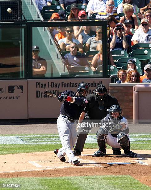Cleveland Indians designated hitter Carlos Santana hits a single home run in the first inning of a baseball game against the Detroit Tigers in...