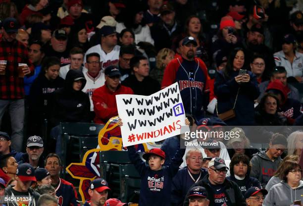 Cleveland Indians fans hold signs supporting the Indians' win streak in the ninth inning against the Baltimore Orioles at Progressive Field on...