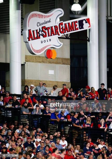 Cleveland Indians fans watch the game against the Minnesota Twins during the seventh inning under the logo for the 2019 AllStar game at Progressive...
