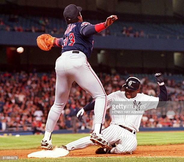 Cleveland Indians first baseman Eddie Murray reaches for the errant throw from second baseman Carlos Baerga as the New York Yankees' Tim Raines...