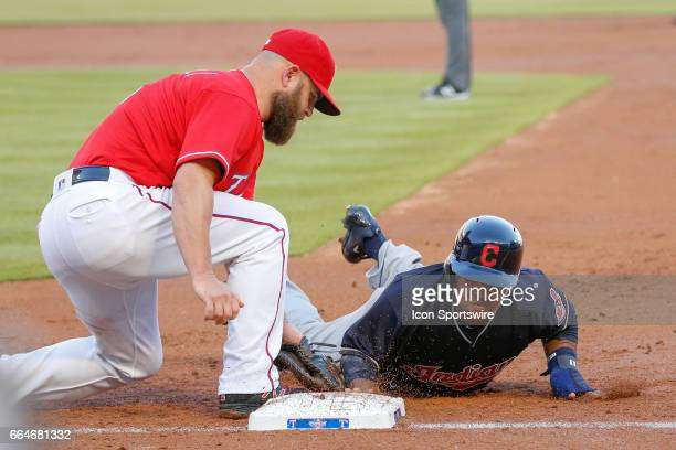 Cleveland Indians Infield Jose Ramirez dives in just under the tag of Texas Rangers First base Mike Napoli during the MLB opening day baseball game...