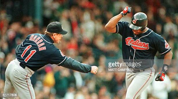 Cleveland Indians left fielder Albert Belle grins as he prepares to bang fists with Indians third base coach Toby Harrah in the fourth inning 24 May...