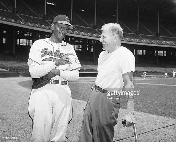 Cleveland Indians owner and president Bill Veeck Jr on crutches talks to pitcher Satchel Paige Paige just joined the Indians after a long career in...