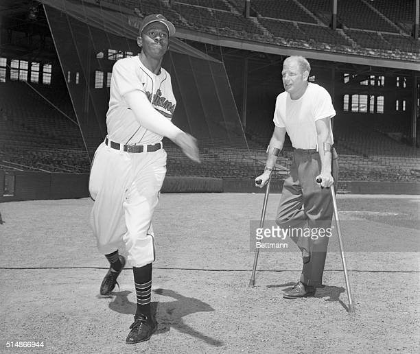 Cleveland Indians owner Bill Veeck, Jr., standing on crutches, watches pitcher Satchel Paige warm up.