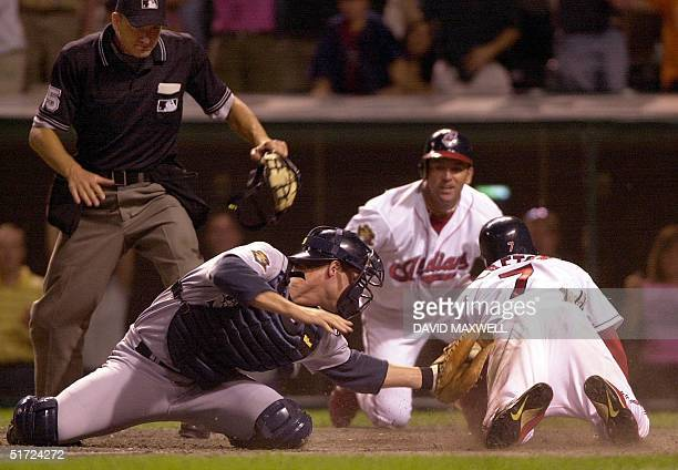 Cleveland Indians second baseman Kenny Lofton scores the gamewinning run ahead of the tag attempt by Seattle Mariners catcher Tom Lampkin as Indians...