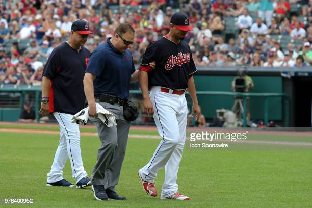 Cleveland Indians starting pitcher Carlos Carrasco leaves the field with a member of the Indians training staff followed by Cleveland Indians manager...