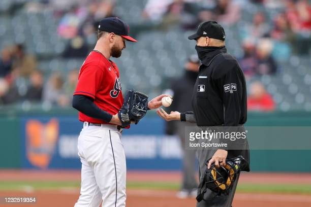 Cleveland Indians starting pitcher Logan Allen hands the baseball to home plate umpire Andy Fletcher during the second inning of the Major League...