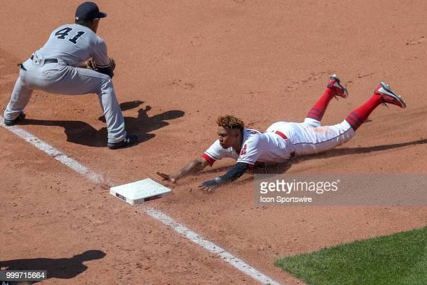 Cleveland Indians third baseman Jose Ramirez slide head first into third base ahead of the throw to New York Yankees third baseman Miguel Andujar as...