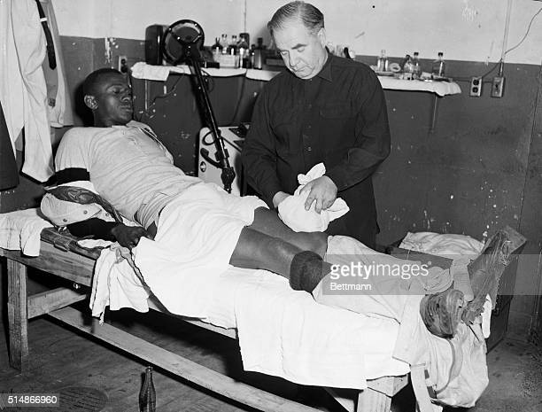 """Cleveland Indians trainer Max """"Lefty"""" Weisman puts an ice pack on the leg of pitcher Satchel Paige. Paige wrenched it during practice."""