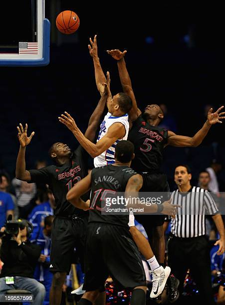 Cleveland Melvin of the DePaul Blue Demons puts up a shot over Cheikh Mbodj Jermaine Sanders and Justin Jackson of the Cincinnati Bearcats on his way...