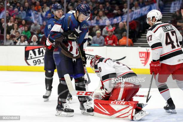 Cleveland Monsters center Calvin Thurkauf stands over Grand Rapids Griffins goalie Tom McCollum after McCollum made a save during the second period...