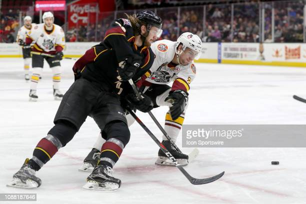 Cleveland Monsters center Ryan MacInnis controls the puck as Chicago Wolves defenceman Nic Hague defends during the second period of the American...