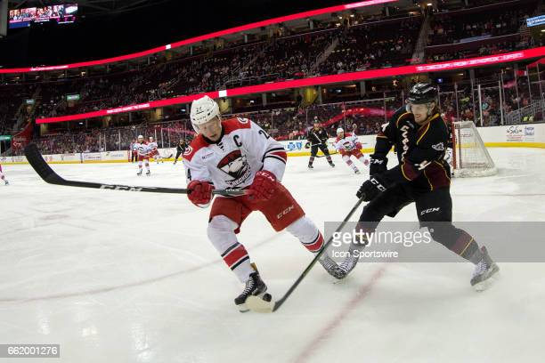 Cleveland Monsters D Dean Kukan battles Charlotte Checkers C Patrick Brown for the puck during the first period of the AHL hockey game between the...