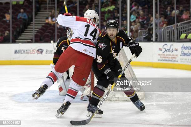 Cleveland Monsters D Jaime Sifers defends against Charlotte Checkers LW Levko Koper during the first period of the AHL hockey game between the...