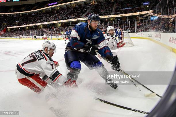 Cleveland Monsters defenceman Brady Austin and Grand Rapids Griffins right wing Evgeny Svechnikov battle for the puck during the first period of the...