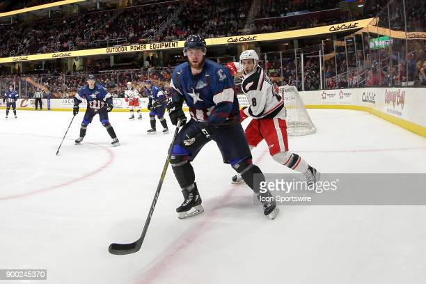 Cleveland Monsters defenceman Brady Austin and Grand Rapids Griffins left wing Matt Lorito follow the puck into the corner during the third period of...