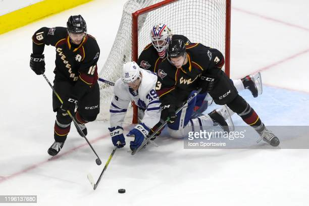 Cleveland Monsters defenceman Dillon Simpson and Cleveland Monsters defenceman Andrew Peeke battle Toronto Marlies center Hudson Elynuik for the puck...