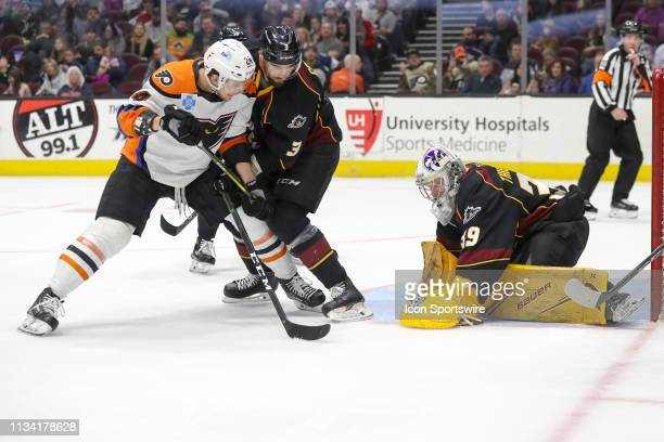 Cleveland Monsters defenceman Tommy Cross defends Lehigh Valley Phantoms left wing Carsen Twarynski as Cleveland Monsters goalie Brad Thiessen covers...