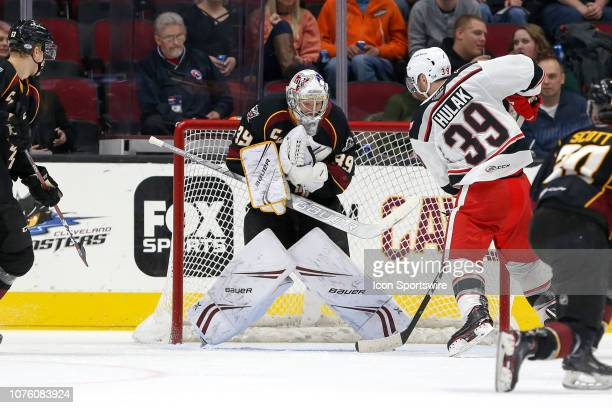 Cleveland Monsters goalie Brad Thiessen cluches the puck to his body after making a save during the second period of the American Hockey League game...