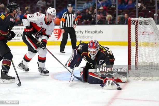 Cleveland Monsters goalie Jean-Francois Berube reaches for a loose puck as Cleveland Monsters defenceman Adam Clendening defends against Belleville...