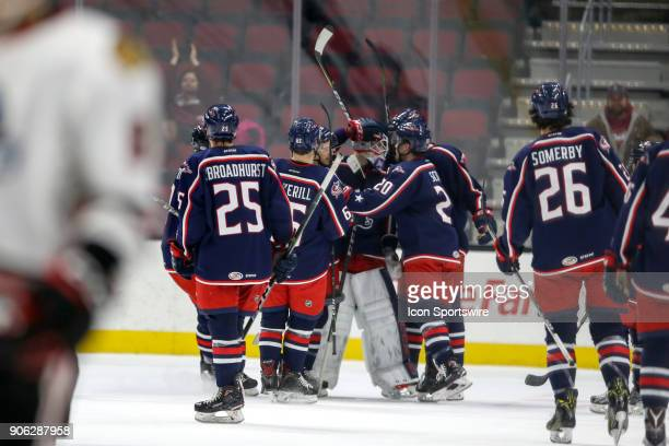 Cleveland Monsters goalie Matiss Kivlenieks is congratulated by teammates after making the final stop in the shootout of the American Hockey League...