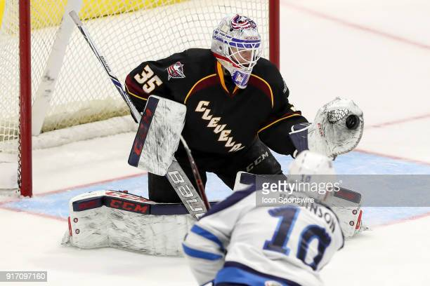 Cleveland Monsters goalie Matiss Kivlenieks makes a glove save to shot the shot of Manitoba Moose right wing Buddy Robinson during the third period...