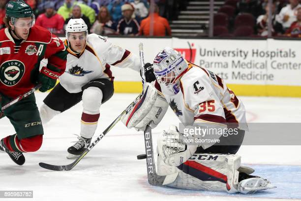 Cleveland Monsters goalie Matiss Kivlenieks makes a save as Iowa Wild right wing Christoph Bertschy and Cleveland Monsters defenceman Blake...