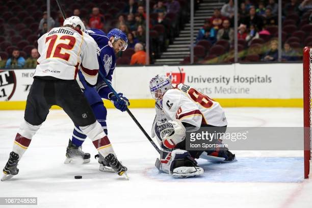 Cleveland Monsters goalie Matiss Kivlenieks reaches for a loose puck as Cleveland Monsters center Ryan MacInnis defends Syracuse Crunch left wing...