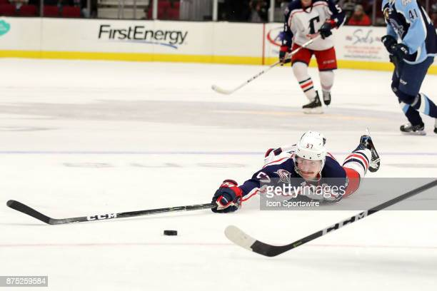Cleveland Monsters left wing Paul Bittner reaches for the puck while flat on the ice during the second period of the American Hockey League game...
